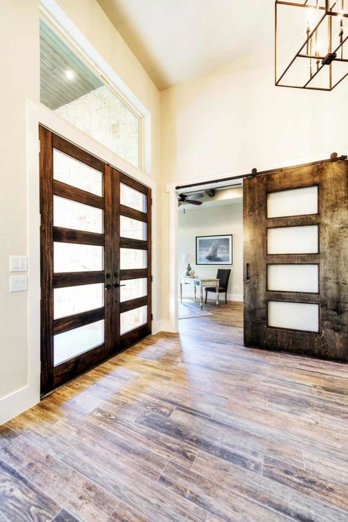 front door entry with hardwood floors and wood and glass doors