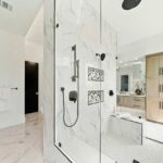 Shower with one wall made of glass, two walls of white ceramic, and one open wall.