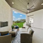Open rest area with a fireplace, three couches, overseeing an open wall to the backyard filled with grass